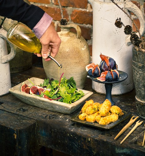 Oil being poured onto a salad on an appetiser buffet