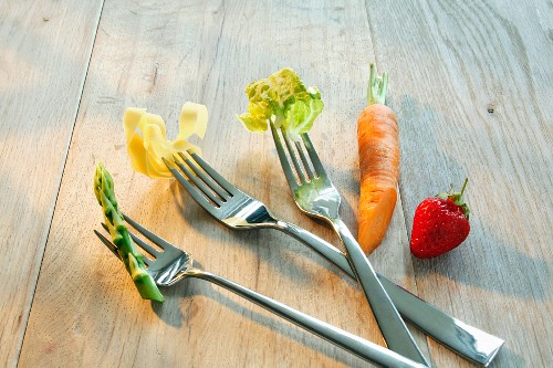 Forks with asparagus, pasta and salad leaves, with a carrot and a strawberry to one side