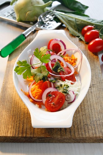 A plate of raw vegetables with onions and parsley pesto