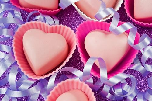 Rosa Schokoladenpralinen in Herzförmchen zwischen Luftschlangen