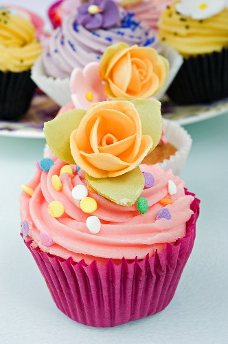 still life of a row of coloured cup cakes decorated with orange rose flowers on top in their cake papers on a white table with other cup cakes in the background