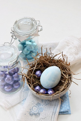 Mini chocolate eggs in preserving jars and a painted egg in a nest for Easter