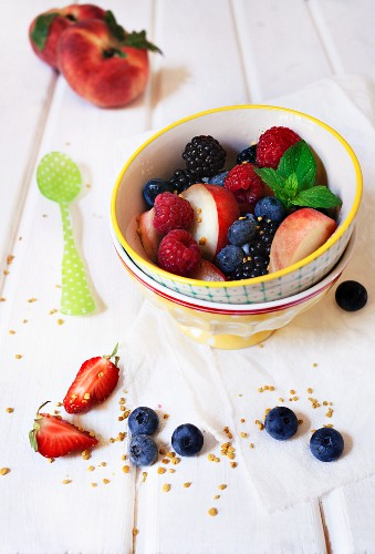 Colourful summer fruit salad with fresh mint and chopped nuts