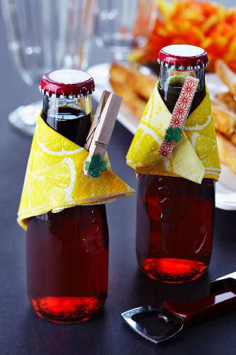 Drink bottles decorated with napkins and clothes pegs