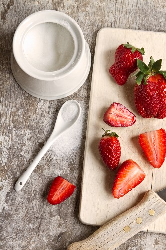 Strawberries on a chopping board; scattered sugar to one side
