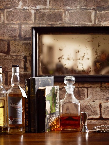 Various types of whisky on a wooden bar against a rustic wall