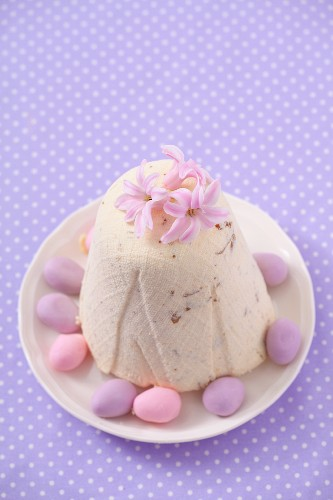 Pashka (quark dessert, Poland) with pink flowers and marzipan eggs for Easter