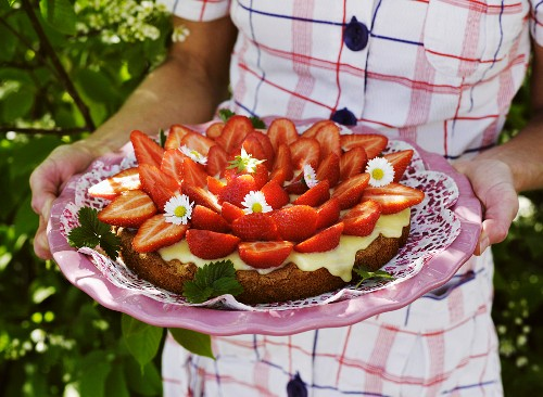 A woman holding a strawberry cake with vanilla cream
