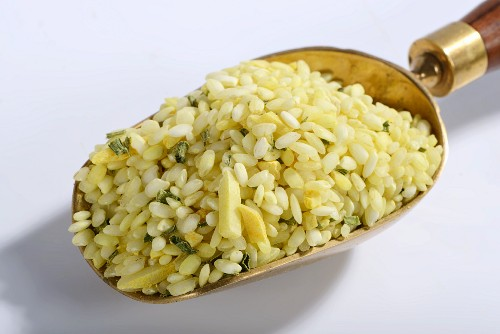 Vialone Nano risotto rice with almonds, lemon oil, turmeric and chives on a brass scoop