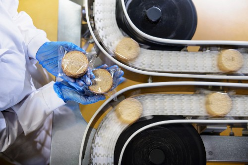 A worker checking packaged biscuits on a conveyor belt