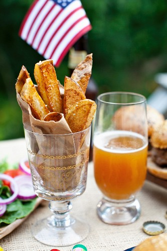 Potato wedges on a table outside, in the background buffalo burgers and a US flag