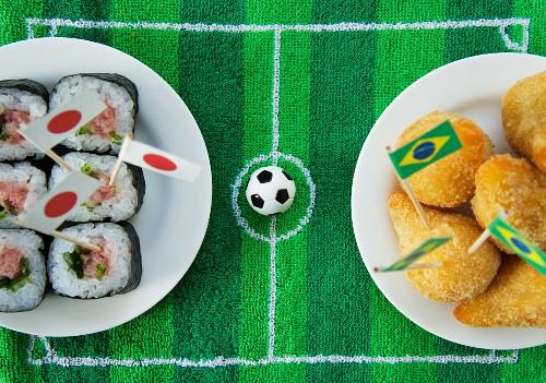 Sushi (Japan) and salgadinhos (Brazil) with football-themed decoration