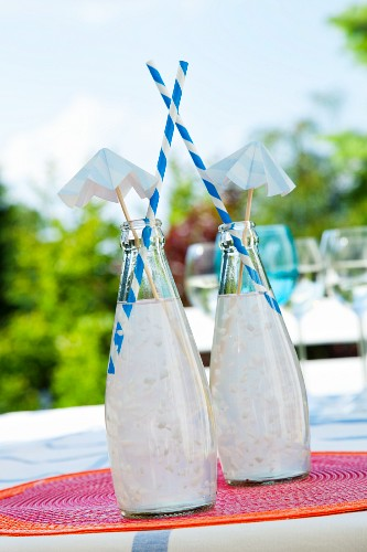 Two bottles with coconut cocktails, straws and paper umbrellas