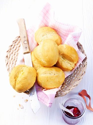 Yeast bread rolls in a bread basket, dish of marmalade