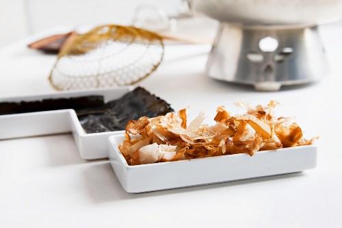 Ingredients for Japanese dashi stock: bonito flakes and kelp (konbu) with utensils