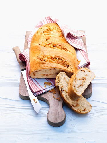 Onion bread on a chopping board, partly sliced