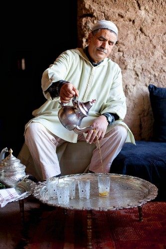 A North African man pouring tea into glasses