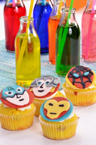 Cupcakes decorated with superheroes, and colourful drinks in bottles with drinking straws