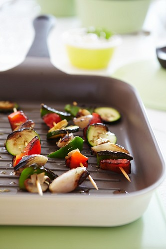 Vegetable skewers of peppers, courgette and onions in a griddle pan