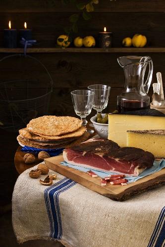 Rustikale Südtiroler Brotzeit mit Rohschinken, Schüttelbrot, Nüssen, Käse und Wein