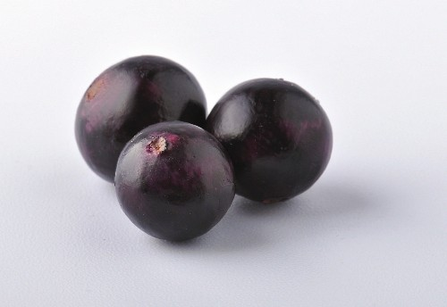 Three acai berries against a white background (close-up)
