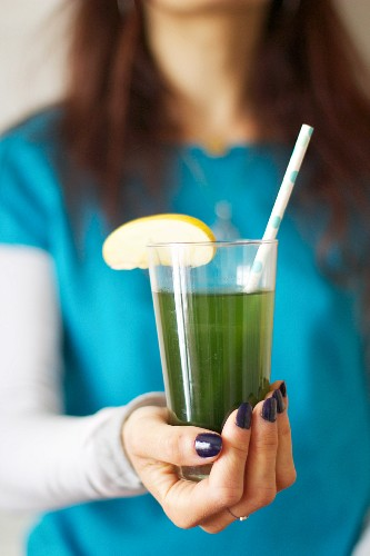 A woman holding a glass of apple juice with chlorella (freshwater algae)