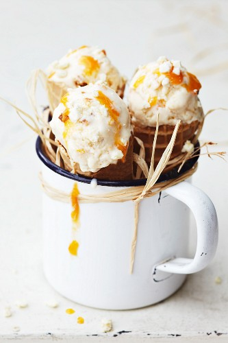 Three ice cream cones with apricot ice cream in an enamel mug