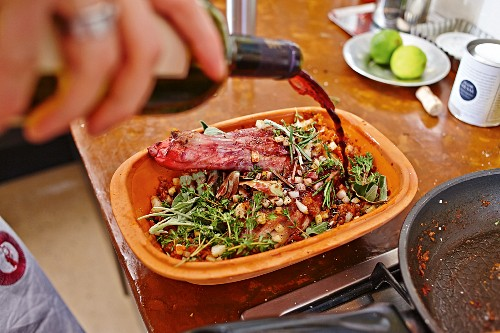 Red wine being poured over lamb shoulder in a clay roasting dish