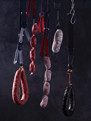 Assorted sausages hanging on braces