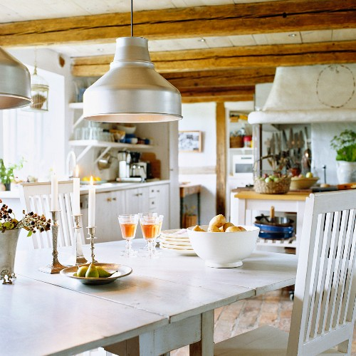 Dining table in rustic kitchen with wood-beamed ceiling