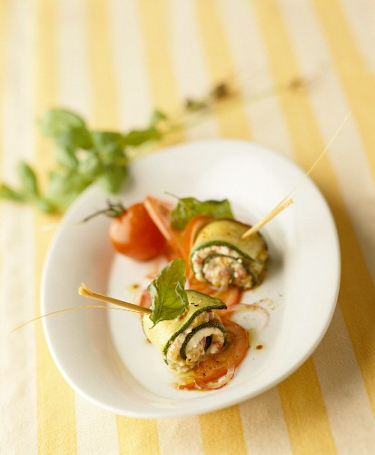 Slices of courgette rolled around tomatoes and basil