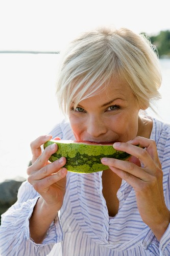A woman eating a watermelon by the sea in the archipelago of Stockholm, Sweden.