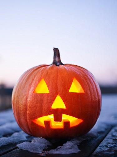 Beleuchteter Halloweenkürbis mit geschnitzem Gesicht