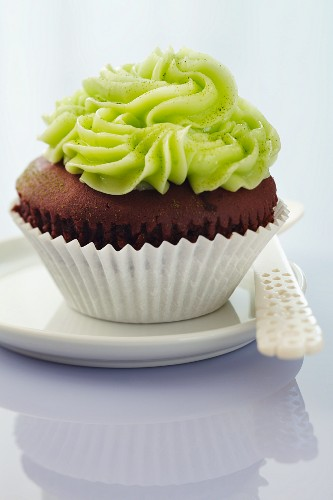 A chocolate cupcake topped with matcha buttercream