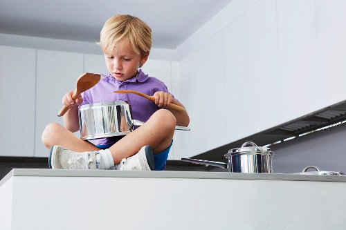 Boy sitting on kitchen counter playing drums with pans and wooden spoons