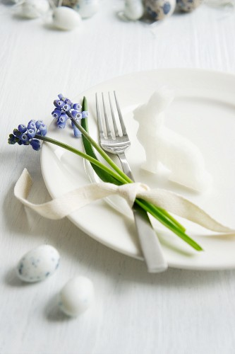 A place setting decorated with a radish rabbit and grape hyacinths