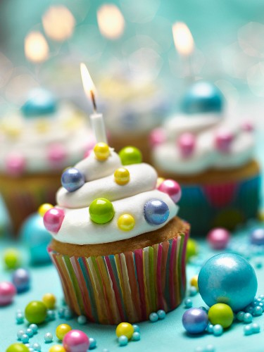 Festively Decorated Cupcakes with Lit Candles