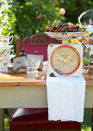 Set table in sunny garden; bowl of fresh berries on a kitchen scale converted into a clock