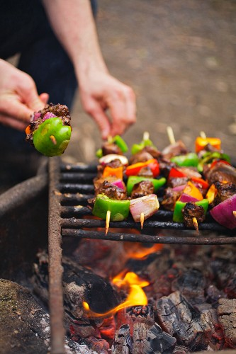 A Man Grilling Kabobs over a Campfire