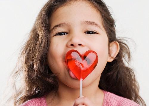 Studio shot of Hispanic girl licking heart lollipop