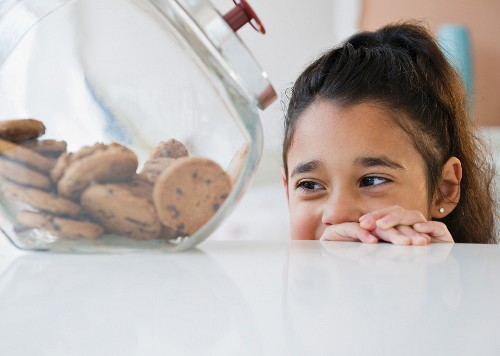 Mixed race girl looking at cookies in cookie jar