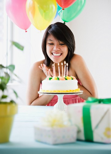 Asian woman about to blow out birthday candles