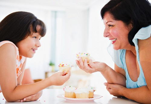 Hispanic mother and daughter eating cupcakes