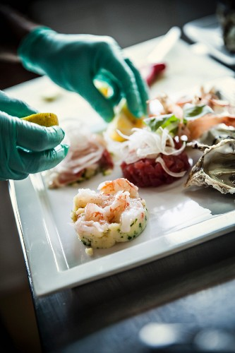 A chef arranging a fish dish on a white porcelain plate