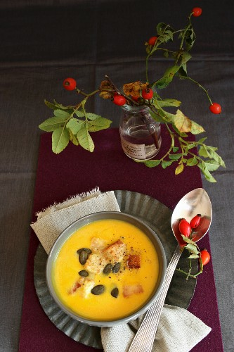 Cream of pumpkin soup with pumpkin seeds and a sprig of rosehips decorating the table