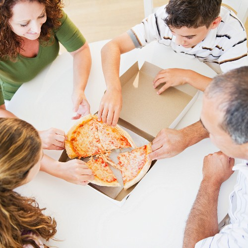 Hispanic family eating pizza together