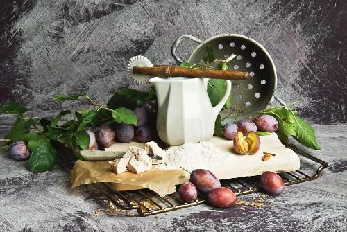 Plums, flour, yeast and kitchen utensils