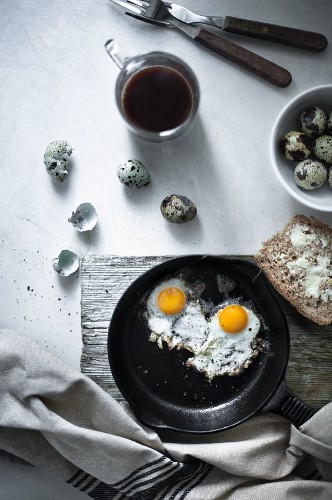 Quail eggs fried with a buttered bread and a mug of coffee.
