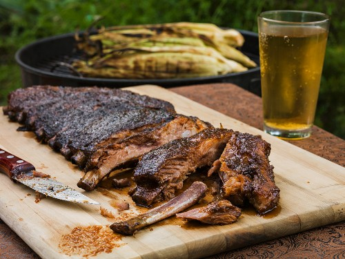 BBQ ribs outside on a cutting board with the first few segments cut exposing the meat with gilled corn and a beverage in the background