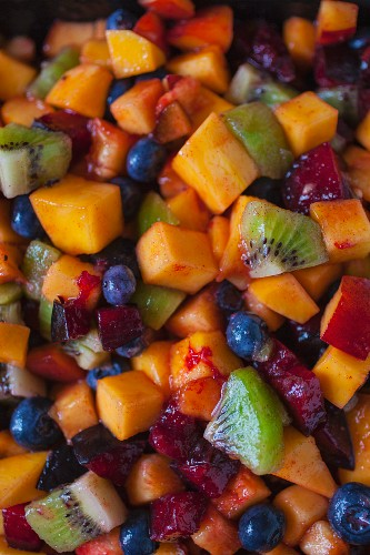 Overhead of colorful fruit salad showing blueberries, mango, plum and kiwi filling the frame